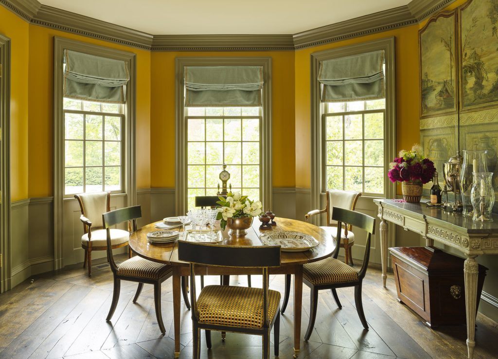 An apricot orange colored, octagonal dinning room with antiques and custom window treatments.