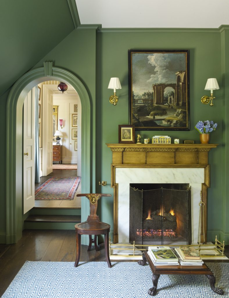 Green walls and sconces in a chanrming master bedroom with a fireplace and antiques.