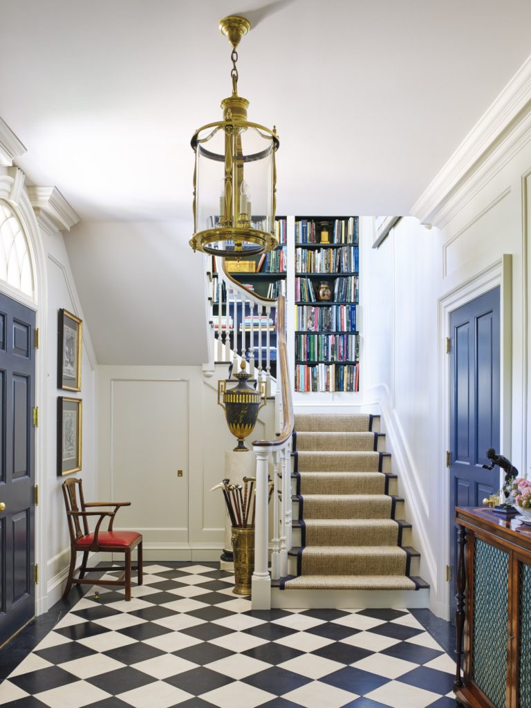 Beautiful and classical Georgian entryway with a black and white marble floor, brass lantern, and sisal stair runner. Navy blue doors.